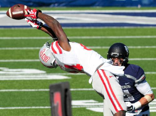 UNLV's Kendal Keys, left, attempts a catch during an NCAA college football game gainst Utah State, Saturday, Oct. 25, 2014, in Logan, Utah. (AP Photo/The Herald Journal, John Zsiray)