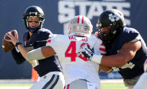 Utah State quarterback Craig Harrison, left, looks to pass during an NCAA college football game against UNLV, Saturday, Oct. 25, 2014, in Logan, Utah. (AP Photo/The Herald Journal, John Zsiray)