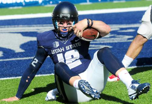 Utah State quarterback Craig Harrison gets up after running the ball during an NCAA college football game against UNLV, Saturday, Oct. 25, 2014, in Logan, Utah. (AP Photo/Herald Journal, John Zsiray)