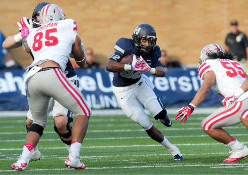 Utah State's Joe Hill, center, runs the ball during an NCAA college football game against UNLV, Saturday, Oct. 25, 2014, in Logan, Utah. (AP Photo/The Herald Journal, John Zsiray)