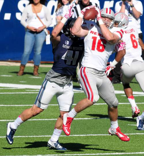 UNLV's Taylor Barnhill (16) makes a catch as Utah State's Nick Vigil attempts to break up the play during an NCAA college football game, Saturday, Oct. 25, 2014, in Logan, Utah. (AP Photo/The Herald Journal, John Zsiray)