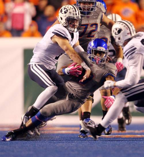 Boise State running back Jeremy McNichols is brought down by BYU defenders during an NCAA college football game in Boise, Idaho, Friday, Oct. 24, 2014. (AP Photo/The Idaho Statesman, Kyle Green) MANDATORY CREDIT; LOCAL TELEVISION OUT (KTVB 7)