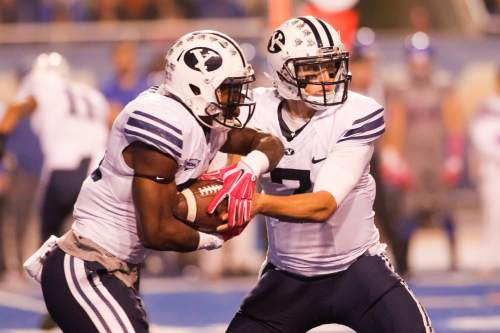 BYU quarterback Christian Stewart (7) hands off the ball to running back Jamaal Williams during the second quarter of an NCAA college football game against Boise State in Boise, Idaho, Friday, Oct. 24, 2014. (AP Photo/Otto Kitsinger)