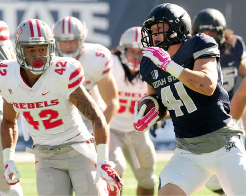 Utah State's Nick Vigil, right, runs the ball as UNLV's Peni Vea gives chase during an NCAA college football game, Saturday, Oct. 25, 2014, in Logan, Utah. (AP Photo/The Herald Journal, John Zsiray)