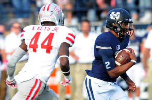 Utah State's quarterback Kent Myers, right, runs the ball as UNLV's Kenny Keys gives chase during an NCAA college football game, Saturday, Oct. 25, 2014, in Logan, Utah. (AP Photo/The Herald Journal, John Zsiray)