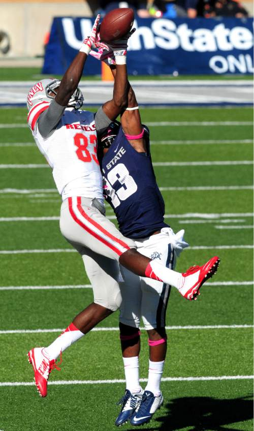 UNLV's Devonte Boyd (83) makes a catch while guarded by Utah State's Jalen Davis during an NCAA college football game, Saturday, Oct. 25, 2014, in Logan, Utah. (AP Photo/The Herald Journal, John Zsiray)