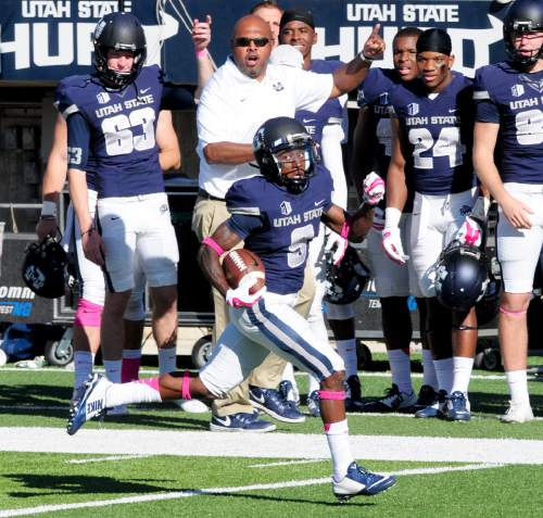 Utah State's JoJo Natson runs the ball downfield for a touchdown during an NCAA college football game against UNLV, Saturday, Oct. 25, 2014, in Logan, Utah. (AP Photo/The Herald Journal, John Zsiray)