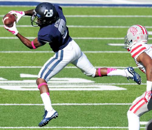 Utah State's JoJo Natson, left, makes a catch during an NCAA college football game against UNLV, Saturday, Oct. 25, 2014, in Logan, Utah. (AP Photo/The Herald Journal, John Zsiray)
