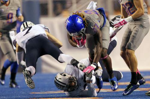 Boise State running back Jay Ajayi (27) is tripped by BYU defenders during an NCAA college football game in Boise, Idaho, Friday, Oct. 24, 2014. (AP Photo/The Idaho Statesman, Kyle Green) MANDATORY CREDIT; LOCAL TELEVISION OUT (KTVB 7)