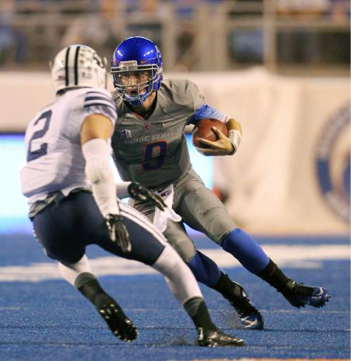 Boise State quarterback Grant Hedrick (9) looks to evade BYU defensive back Dallin Leavitt (2) during an NCAA college football game in Boise, Idaho, Friday, Oct. 24, 2014. (AP Photo/The Idaho Statesman, Kyle Green) MANDATORY CREDIT; LOCAL TELEVISION OUT (KTVB 7)