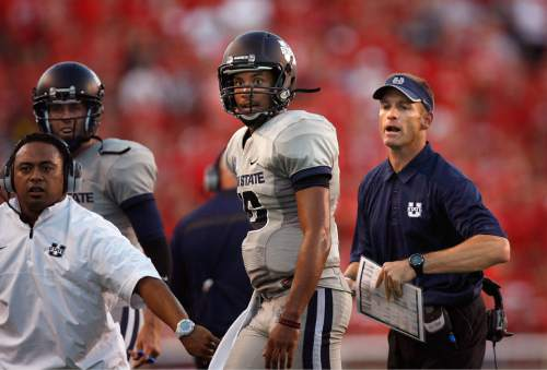 Scott Sommerdorf   |  The Salt Lake Tribune Utah State QB Chuckie Keeton walks to the sideline after his TD toss to give USU a 17-14 halftime lead over Utah, as head coach Matt Wells tries to get his celebrating players behind the sidelines, Thursday, August 29, 2013.