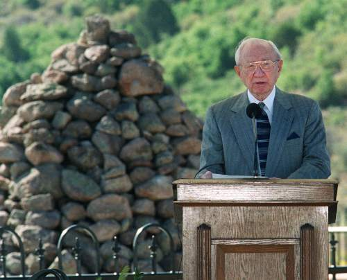 LDS Church President Gordon B. Hinckley dedicates the Mountain Meadow Massacre Memorial site. The piles of stones behind him are part of the monument.  (Al Hartmann/The Salt Lake Tribune)