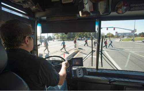 Steve Griffin  |  The Salt Lake Tribune   University of Utah shuttle operator Nik Nielson, takes the  university's new wireless electric bus for a test ride on the campus in Salt Lake City, Tuesday, October 28, 2014. The bus starts running this week at the University of Utah. It was built with a $2.7 million federal grant and uses a charging track at the school's bus stop neat the Special Events Center