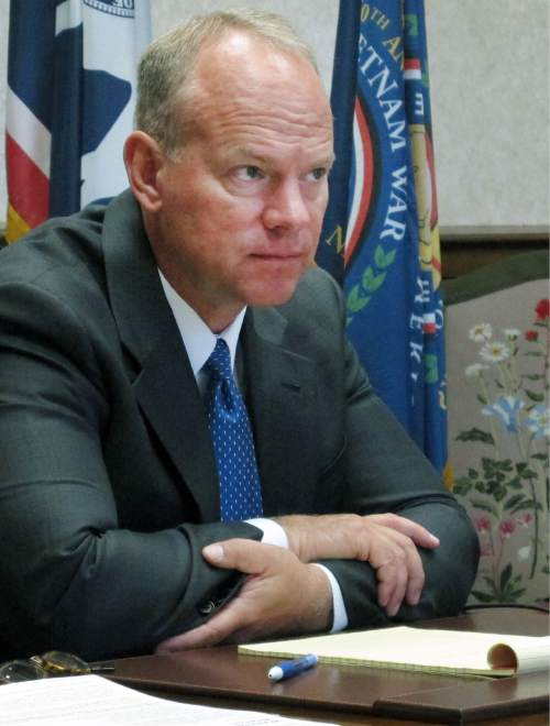 Wyoming Gov. Matt Mead sits at a desk at the state Capitol in Cheyenne on Thursday, Aug. 21, 2014. Mead said he expects to inform state lawmakers early next year of the best deal the federal government is willing to offer if Wyoming agrees to expand the federal Medicaid program to cover more low-income people. (AP Photo/Ben Neary)