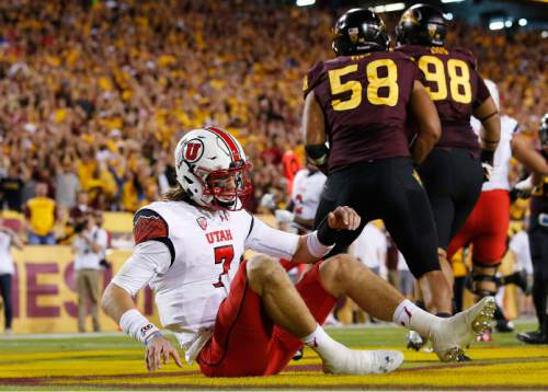 Utah's Travis Wilson (7) sits on the turf in the end zone after being pressured by Salamo Fiso (58) and Mo Latu (98) in the first half of an NCAA college football game on Saturday, Nov. 1, 2014, in Tempe, Ariz. (Photo/Ross D. Franklin)