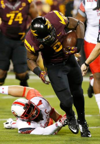 Arizona State's Kalen Ballage, right, breaks the tackle of Utah's Brian Blechen (4) in the first half of an NCAA college football game on Saturday, Nov. 1, 2014, in Tempe, Ariz. (Photo/Ross D. Franklin)