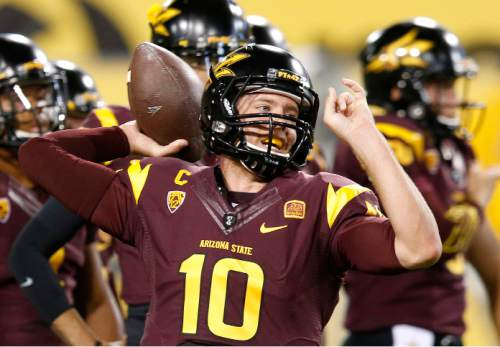 Arizona State's Taylor Kelly throws a pass as he warms up prior to an NCAA college football game against Utah on Saturday, Nov. 1, 2014, in Tempe, Ariz. (Photo/Ross D. Franklin)