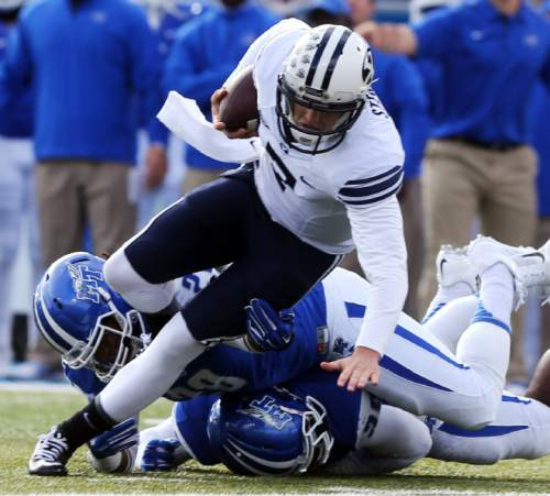 BYU quarterback Christian Stewart, top, is tackled by Middle Tennessee defenders T.T. Barber, bottom, and Christian Henry while rushing on a keeper in the first quarter of an NCAA college football game Saturday, Nov. 1, 2014, in Murfreesboro, Tenn. (AP Photo/The Daily News Journal, John A. Gillis) NO SALES