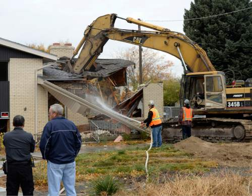Al Hartmann  |  The Salt Lake Tribune Cottonwood Heights residents and city officials watch as a backhoe begins the demolition of one of eight homes Monday, Nov. 3, 2014, that will make way for a new city hall at 7550 S. 2300 East.