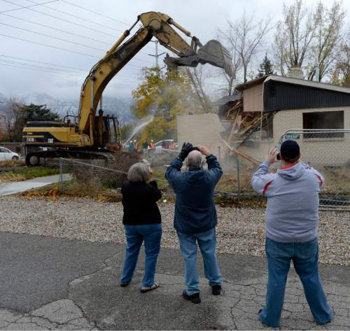 Al Hartmann  |  The Salt Lake Tribune Cottonwood Heights residents watch and take pictures as a backhoe begins the demolition of one of eight homes Monday Nov. 3, 2014, that will make way for a new city hall at 7550 S. 2300 East.