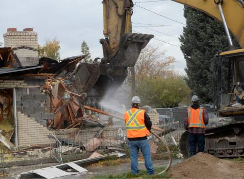 Al Hartmann  |  The Salt Lake Tribune A backhoe begins the demolition of one of eight homes Monday, Nov. 3, 2014, that will make way for a new Cottowood Heights City Hall at 7550 S. 2300 East.