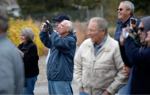 Al Hartmann  |  The Salt Lake Tribune Cottonwood Heights residents watch and take pictures as a backhoe begins the demolition of one of eight homes Monday, Nov. 3, 2014, that will make way for a new city hall at 7550 S. 2300 East.