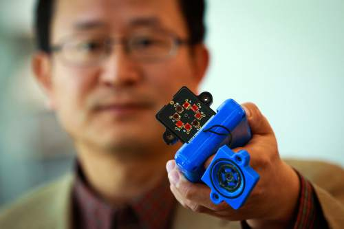 Courtesy  |  Dan Hixon, University of Utah College of Engineering  Ling Zang, a University of Utah professor of materials science and engineering, holds a prototype detector that uses a new type of carbon nanotube material for use in handheld scanners to detect explosives, toxic chemicals and illegal drugs. Zang and colleagues developed the new material, which will make such scanners quicker and more sensitive than todayís standard detection devices. Lingís spinoff company, Vaporsens, plans to produce commercial versions of the new kind of scanner early next year.