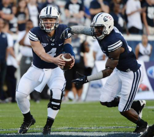 Steve Griffin  |  The Salt Lake Tribune   BYU Cougars quarterback Taysom Hill (4) fakes a handoff to BYU Cougars running back Jamaal Williams (21) during game between BYU and Houston and LaVell Edwards Stadium in Provo, Thursday, September 11, 2014.