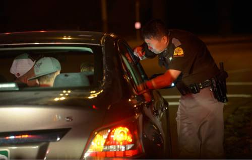 Leah Hogsten  |  The Salt Lake Tribune Utah Highway Patrol Trooper Terry Buck questions a driver about his erratic and dangerous driving while exiting the interstate in October 2014.