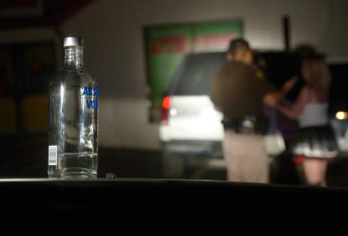 Leah Hogsten  |  The Salt Lake Tribune Utah Highway Patrol Trooper Terry Buck investigates the scene of a DUI where a near empty bottle of vodka was found in the vehicle, October 31, 2014.
