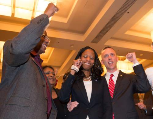 Steve Griffin  |  The Salt Lake Tribune   Mia Love pumps her fist with her husband, Jason, right, and her father, Maxime Bourdeau, as she is introduced as the winner of her congressional race in Utah's 4th district  Salt Lake City, Wednesday, November 5, 2014.