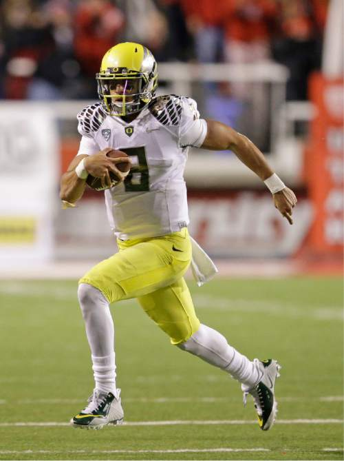 Oregon quarterback Marcus Mariota (8) carries the ball against Utah in the fourth quarter during an NCAA college football game Saturday, Nov. 8, 2014, in Salt Lake City. Oregon  won 51-27. (AP Photo/Rick Bowmer)