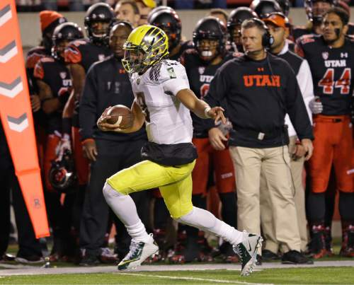 Oregon quarterback Marcus Mariota (8) carries the ball in the first quarter during an NCAA college football game against Utah on Saturday, Nov. 8, 2014, in Salt Lake City. (AP Photo/Rick Bowmer)