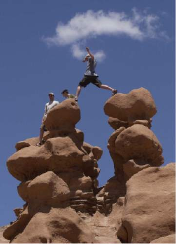 """Sight-seer leaps from one """"goblin"""" to another on a warm Memorial Day in Goblin Valley State Park Photo by Trent Nelson; 05.27.2002, 1:43:40 PM"""
