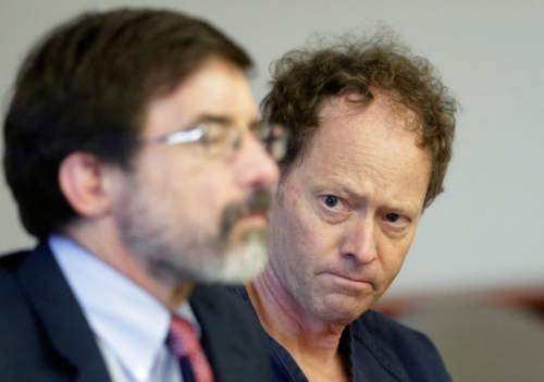 """FILE - John Brickman Wall, a Salt Lake City pediatrician awaiting trial on murder in his ex-wife's death, looks at his attorney Fred Metos, left, during his appearance in court Friday, May 9, 2014, in Salt Lake City.  A Salt Lake City police officer says Wall seemed surprised he was not arrested the night her body was found. Wall's attorney Fred Metos argues his client's statements to police should not be allowed at an upcoming murder trial because they were made under """"psychological and physical coercion"""" by the detectives. (AP Photo/Rick Bowmer, Pool)"""