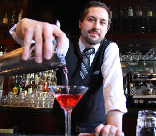 | Courtesy Bambara Bartender Austin Craig pours a drink at Bambara. Gov. Gary Herbert said liquor laws are not hurting Utah.