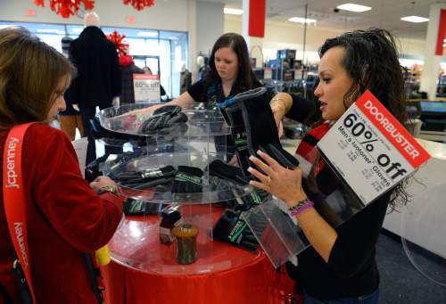 Scott Sommerdorf   |  The Salt Lake Tribune In this file photo, store employees restock the shelves of a department store in Utah on December 21, 2013.
