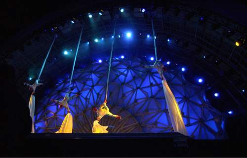 Steve Griffin     The Salt Lake Tribune  Acrobats slide down long pieces of material onto the stage at the Olympic Medals Plaza during kicking off the first night of activities in downtown Salt Lake City Feb. 9, 2002. The first medalists of the 2002 Olympics received their medals and the Dave Mathews Band performed.