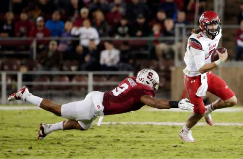 Utah quarterback Travis Wilson is chased by Stanford linebacker James Vaughters during the second half of an NCAA college football game on Saturday, Nov. 15, 2014, in Stanford, Calif. Utah won 20-17 in overtime. (AP Photo/Marcio Jose Sanchez)