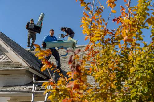 Trent Nelson     The Salt Lake Tribune Tyler Marquardt and Mike Gunter remove two old chimney pipes while Ben Loya installs a new vent during a gas fireplace installation at a home in Salt Lake City, Tuesday November 11, 2014.