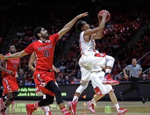 Utah's Brandon Taylor (11) goes to the basket as Ball State's Bik Gill (21) defends during the second half of an NCAA college basketball game Friday, Nov. 14, 2014, in Salt Lake City. Utah won 90-72.  (AP Photo/Rick Bowmer)