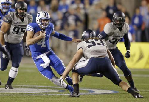 FILE - BYU quarterback Taysom Hill (4) carries the ball as Utah State linebacker Zach Vigil (53) prepares to tackle him during the first quarter ofan NCAA college football game Friday, Oct. 3, 2014, in Provo, Utah. (AP Photo/Rick Bowmer)