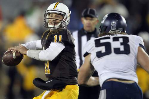 Wyoming quarterback Colby Kirkegaard looks to throw a pass under pressure from Utah State's Zach Vigil during an NCAA college football game Friday, Nov. 7, 2014, in Laramie, Wyo. (AP Photo/Wyoming Tribune Eagle, Miranda Grubbs)