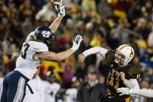Wyoming quarterback Colby Kirkegaard has a pass blocked by Utah State's Zach Vigil in the fourth quarter of an NCAA college football game Friday, Nov. 7, 2014, in Laramie, Wyo. Utah State won 20-3. (AP Photo/Casper Star-Tribune, Ryan Dorgan)