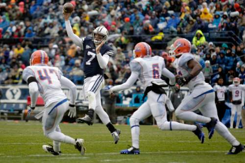 BYU quarterback Christian Stewart (7) throws a pass while being chased by a group of Savannah State defenders during an NCAA college football Saturday, Nov. 22, 2014, in Provo, Utah. (AP Photo/The Daily Herald, Ian Maule) MANDATORY CREDIT