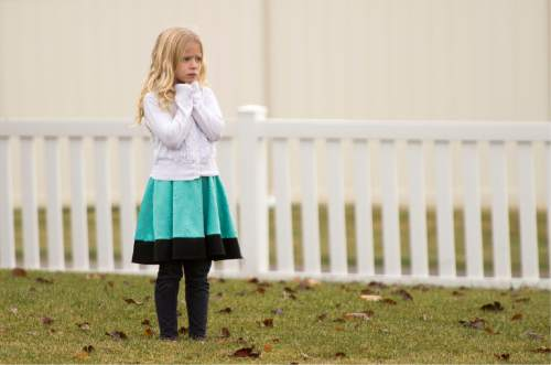 Rick Egan  |  The Salt Lake Tribune  A neighbor girl watches as police investigate a fatal accidental shooting in the 1900 block of Cooper Street in Kaysville, Sunday, November 23, 2014