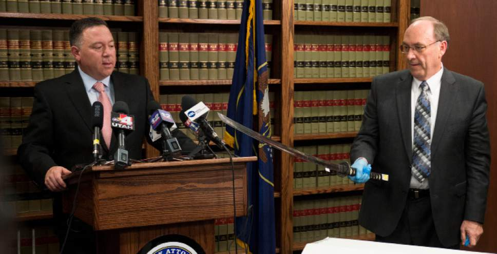 Steve Griffin  |  The Salt Lake Tribune  Utah County Attorney Bureau of Investigations Bureau Chief Jeff Robinson, right, holds the sword carried by Darrien Hunt as Utah County Attorney Jeffrey Buhman addresses the media as he explains the Utah County Attorney's Office's ruling in the officer-involved shooting of Hunt during a press conference in Provo, Monday, November 3, 2014.