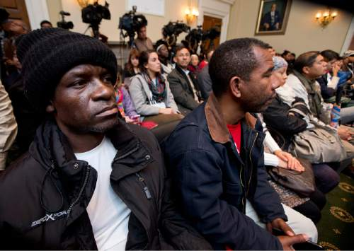 Guillaume Fochie from Cameroon, left, and Otoniel Paz  from Colombia, center, listen to members of Congress fighting for immigration reform, speak about immigration and executive action during a news conference on Capitol Hill in Washington, Tuesday, Dec. 2, 2014.  (AP Photo/Manuel Balce Ceneta)