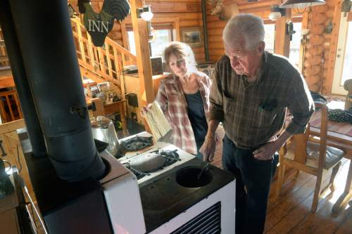 Al Hartmann  |  The Salt Lake Tribune Ray and Joan Cummings stoke the woodburning cook stove in their off-grid cabin on the mountainside near Jordanelle Reservoir. The Cummings family has deep roots in the area spanning several generations. But they, like other landowners, have been caught up in a nasty, expensive, dispute with the Jordanelle Special Service District.
