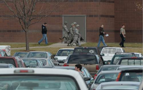 Francisco Kjolseth  |  The Salt Lake Tribune Officials with a bomb sniffing dog exit Fremont High school in Plain City during a lock down after reports of a student seen with a gun on Monday, Dec. 1, 2014.